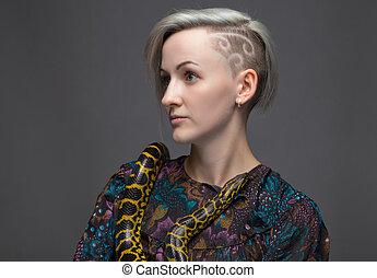 Shaved woman and yellow anaconda