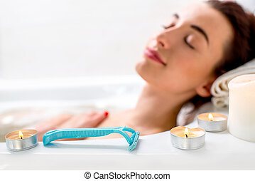 Shaver - Disposable shaver on the bath with lying woman on ...