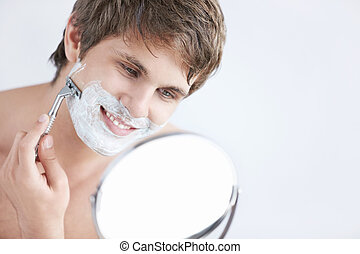 Shaving a man - Young attractive man shaves in the mirror