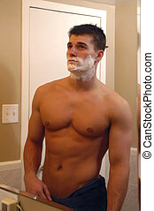 Shaving - A sexy man looking in mirror while shaving