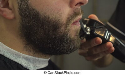 Shaving beard of man in barber shop. Closeup portrait -...