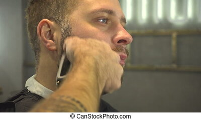 Shaving beard of man in barber shop