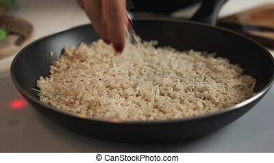 Shaving bits of parmesan cheese into hot risotto in a large...