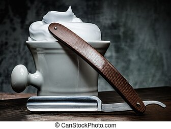 Shaving bowl and straight razor on wooden background