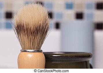 Closeup of a shaving brush and shaving soap mug