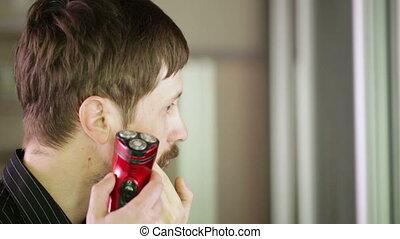 Shaving his mustache in profile to right