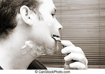Shaving - Man shaving his beard off. Looking in the mirror. ...