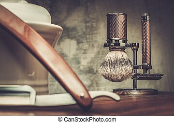 Shaving razors and bowl with foam on wooden background