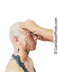 Shaving young man's head