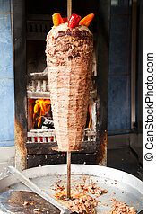 Shawarma meat on rotating spit - Grilled meat used for...