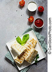 Shawarma pita bread with grilled chicken, shaurma doner, fresh vegetables and cream sauce on a light stone or concrete background. Top view with copy space, concept restaurant fast food.
