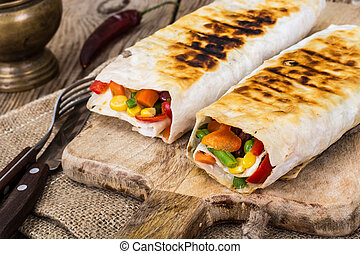 Shawarma with vegetables on a wooden background