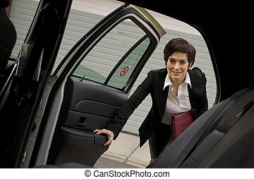 A business woman gets in the cab