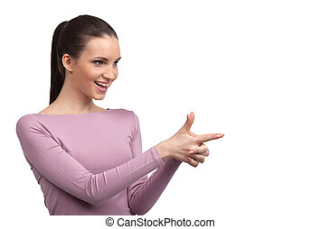 She gets what she wants. Attractive young woman making a gun from fingers and pointing away while standing isolated on white
