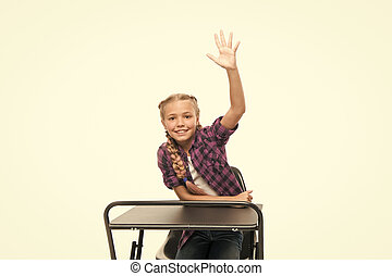 She is a bright student. Small girl student raising hand isolated on white. Little student reciting lesson in class. Cute lyceum student sitting at desk.