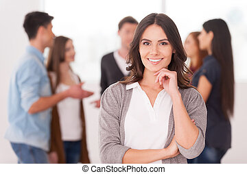 She is a team leader. Confident young woman holding hand on chin and smiling while group of people communicating on background