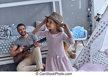 She is his little princess. Young father playing guitar for...