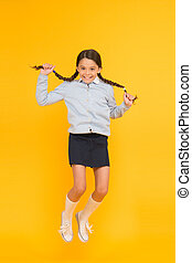 She is hyper. Happy energetic kid jumping on yellow background. Little girl with long hair braids feeling energetic. Small schoolchild getting energetic start to school year. Active and energetic