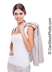 She is pleased with herself. Confident young businesswoman carrying her jacket on shoulder and smiling while standing against white background