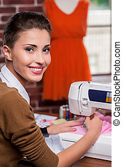 She is the best in fashion industry. Rear view of cheerful female fashion designer working on sewing machine and looking over shoulder while sitting at her working place