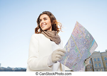She knows the right direction. Beautiful young women looking into the map while standing outdoors