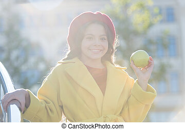 She likes apple best of all fruits. French fashion. Happy little girl holding juicy green apple. child with apple fruit on sunny day. Cheerful kid enjoy apple crop in autumn. Healthy snack for a kid