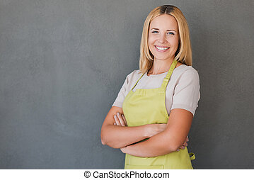 She loves her job. Smiling mature woman in green apron keeping arms crossed and looking at camera while standing against grey background