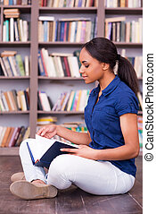 She loves reading. Side view of confident African female student reading a book while sitting on the floor in library