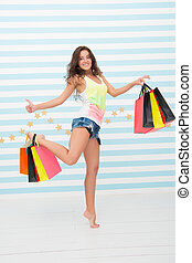 she made a right choice. shopping girl with happy face and thumb up. great sale. time for shopping. happy girl with paperbags on colorful background. carefree and excited buyer showing thumb up.