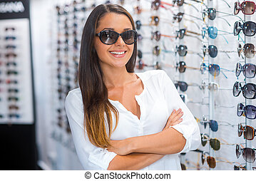 She made her choice. Beautiful young woman in sunglasses keeping arms crossed and smiling while standing in optic store