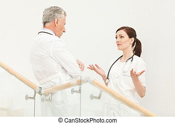 She needs a professional advice. Mature doctor listening to his confused colleague gesturing in front of him