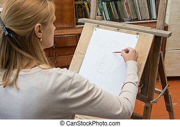 She paints on an easel in a pencil portrait of the artists studio