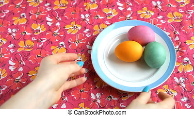 She pick up with pink tablecloth saucer with colorful Easter eggs.