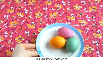 She puts on a pink tablecloth saucer with colorful Easter eggs.