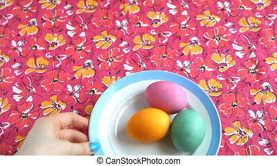 She puts on a pink tablecloth saucer with colorful eggs and Easter cake.