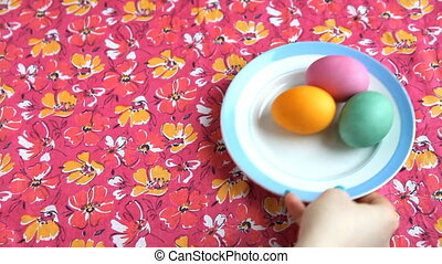 She puts on a pink tablecloth saucer with colorful eggs, Easter cake and spoon.