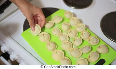 She sculpts dumplings in the kitchen. Cooking food. - She...