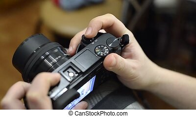 She sets up the camera before shooting. Man turns the wheels of the camera's settings and presses the button on the rear panel. Woman turns on and off camera. She pushes the camera's built-in flash.