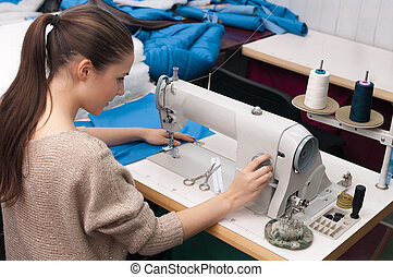 she sews on the sewing machine and turns the switch
