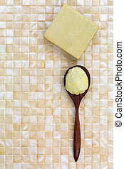 Shea butter in wooden spoon, homemade olive oil soap on yellow tile background