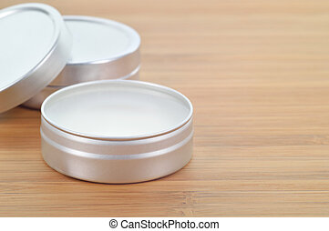 Pure shea butter in metallic tin on wooden background. Perfect lip balm and beauty balm. Plenty of copy space.