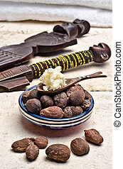 Shea nuts and butter in a spoon - Shea nuts in a dish with a...