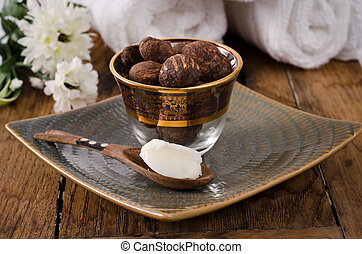 Shea nuts in a glass and wooden spoon - Stil life of shea...