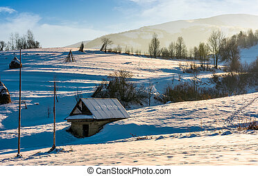 shed on snow covered agricultural hillside. lovely rural...