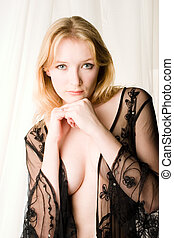 Sheer lingerie - A blond woman in sheer lingerie stands in...