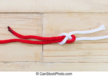 sheet bend knot made with red rope on wooden background.