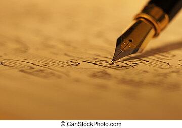 Selective focus of a fountain pen on top of an old sheet music handwritten