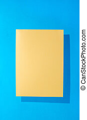Sheet of yellow paper on a blue background for decoration, for text design, for a template