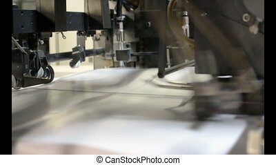 printing - sheets of paper being fed into a printing machine