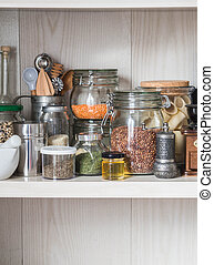Shelf in the kitchen with various jars of cereals and kitchen tools. Glass jars with pasta, lentils, couscous, beans and quinoa. Coffee grinder, honey, spices, herbs, sesame on shelf.
